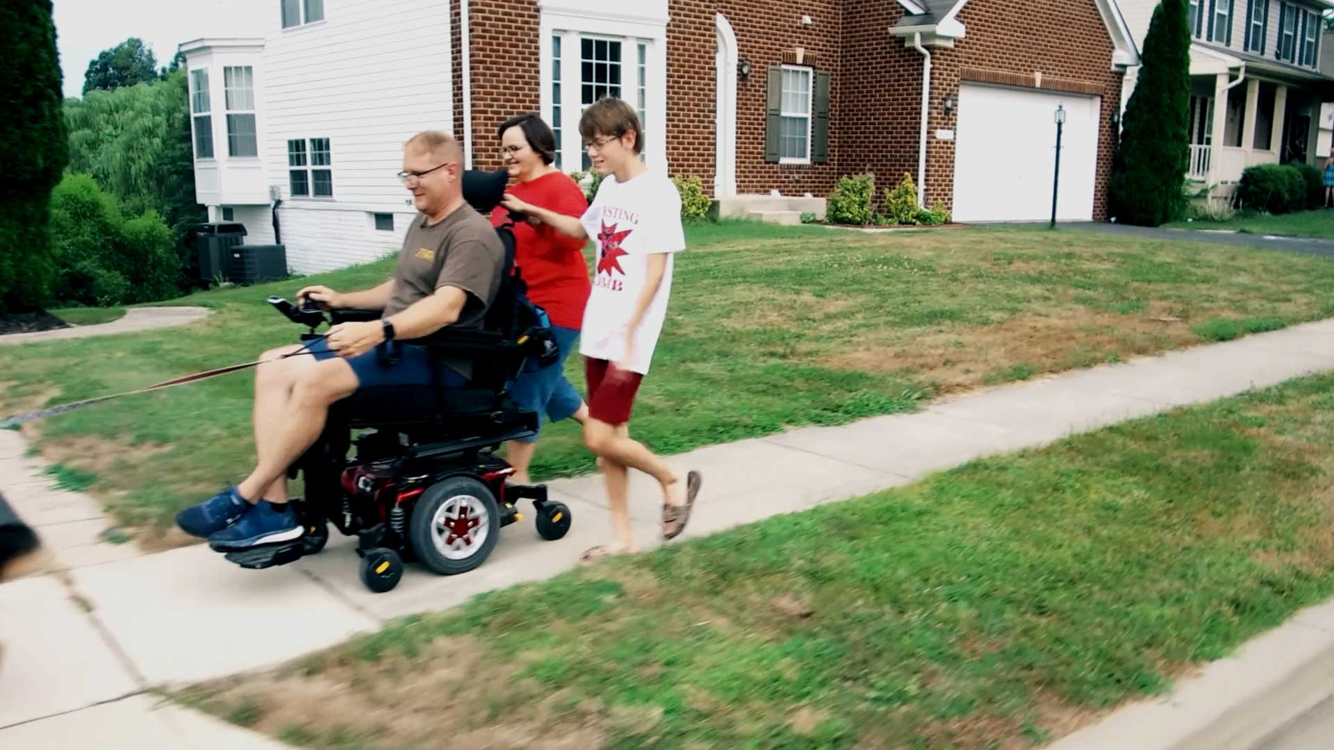 Person in Motorized Wheelchair with Two People Walking
